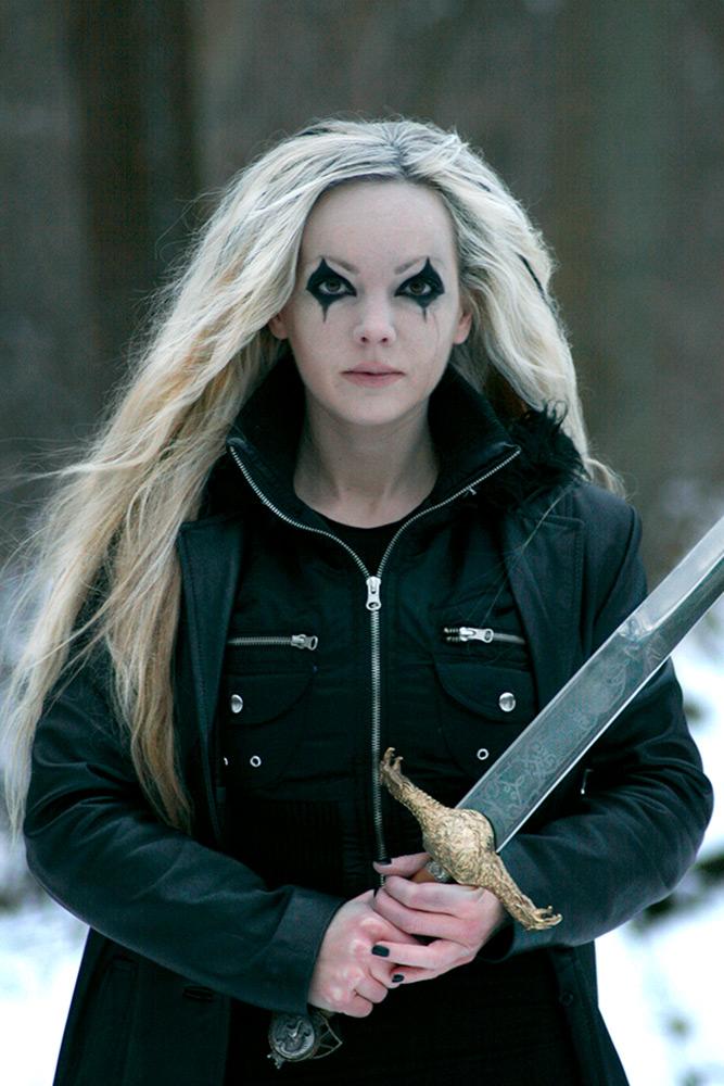 En kvinna med långt ljust hår, håller ett blankt svärd i händerna. Hon är hårt svartsminkad runt ögonen.