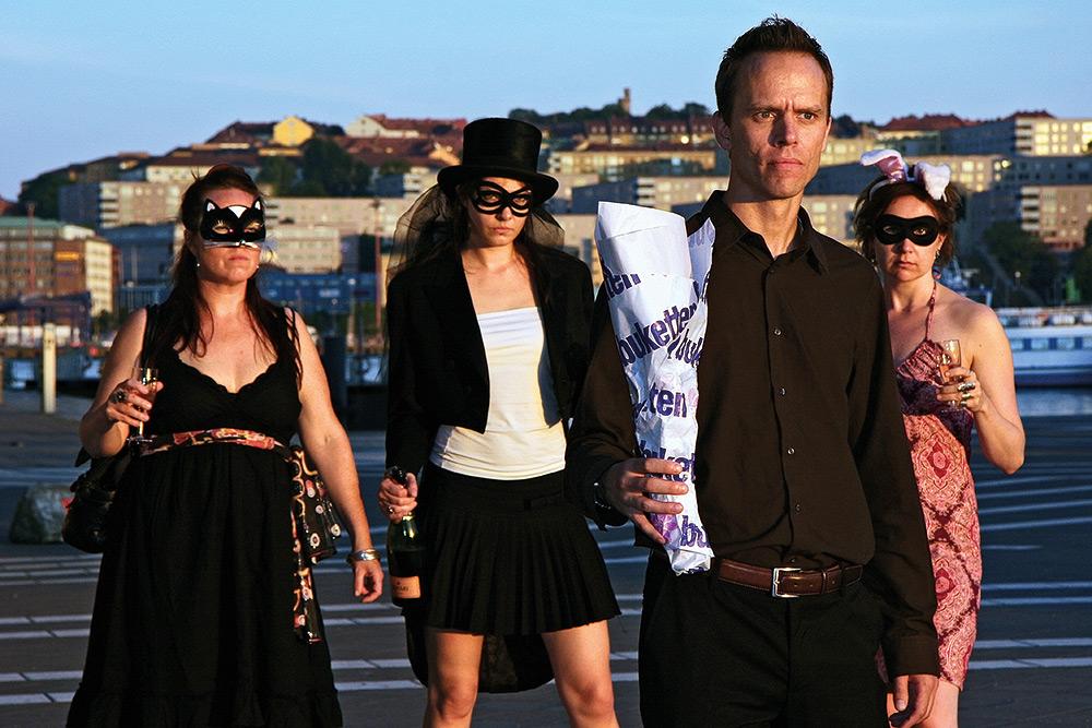 Man med blomsterbukett invirad i papper står framför tre hotfulla festande kvinnor med masker framför sina ansikten. I bakgrunden syns stadsmiljö.