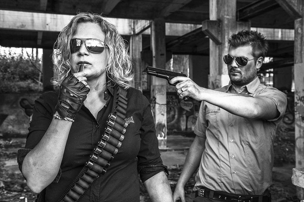 Svartvit bild. Kvinna med solglasögon och patronbälte runt axlarna målar läpparna och en man med skäggstubb och solglasögon pekar på henne med en pistol.