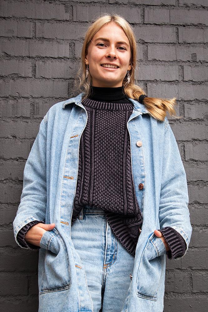 leende ung kvinna med långt ljust hår står med händerna i fickorna i sin jeanskappa och ler framför en grå tegelvägg