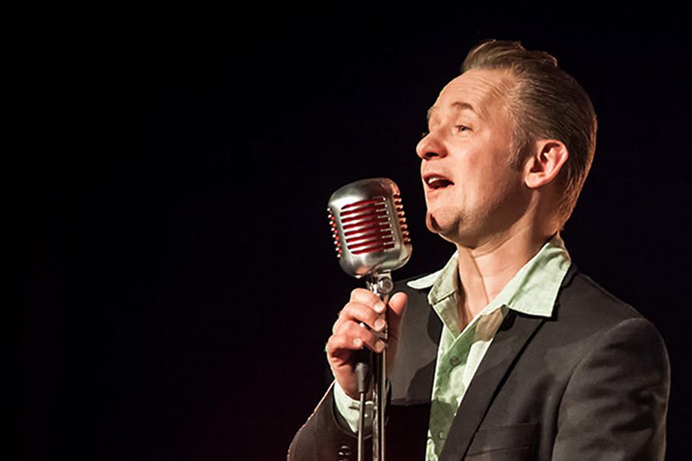 Kingen, artist, man med bakåtstruket hår i kavaj sjunger i gammaldags mikrofon.