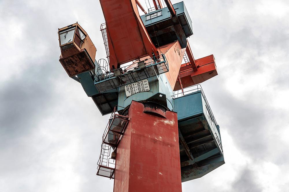 Varvsindustri. Detaljbild nedifrån av blå och orangefärgad hamnkran mot hytt och uppåt.