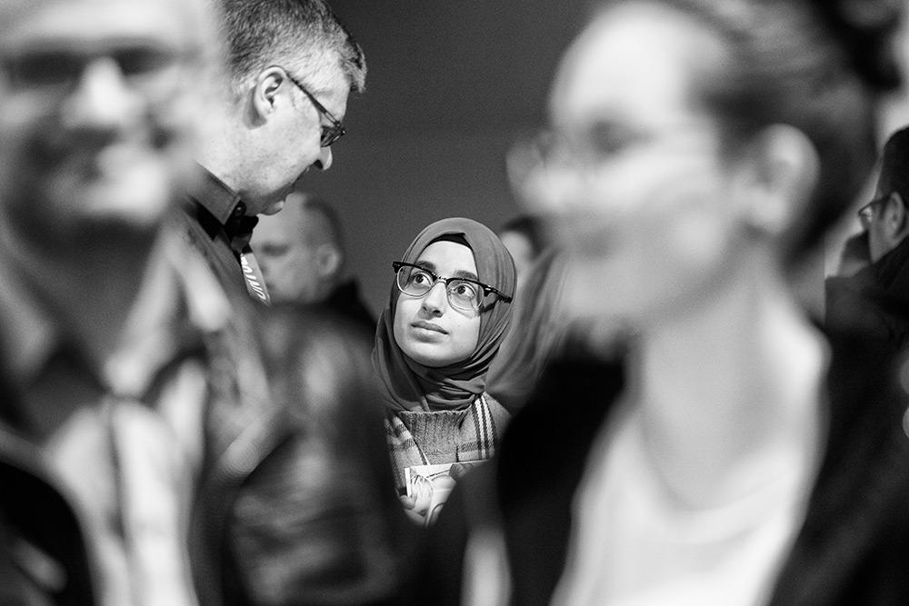 folksamling. äldre man med glasögon tittar ned på ung kvinna i slöja som bär glasögon. hon ser förvånad ut
