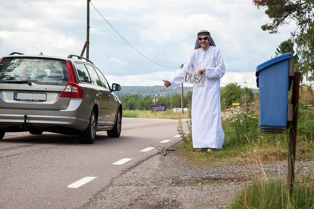 Svensk landsbygd, en silverfärgad volvo passerar en liftare klädd i arabiska kläder och solglasögon som håller en skylt med Dubai skrivet på.