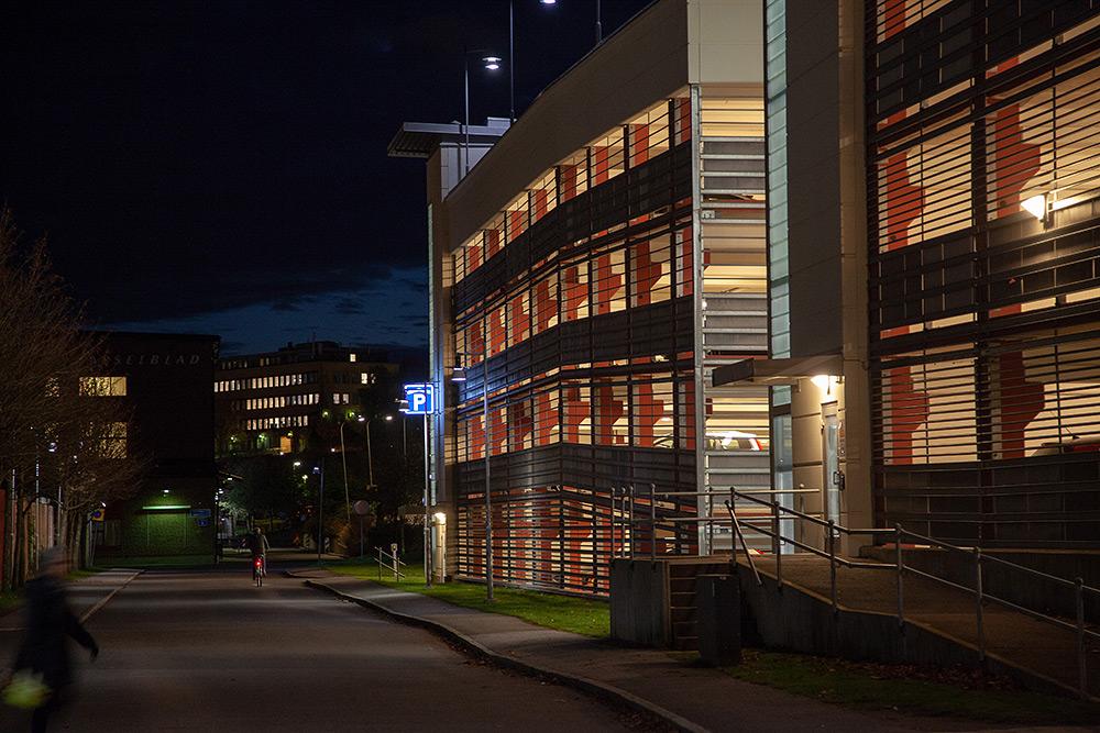 En filmistisk, uttrycksfull bild av ett ljussatt parkeringshus som lyser upp en gata där en kvinna går förbi. En cyklist skymtar långt bort och en blå p-skylt lyser på fasaden.