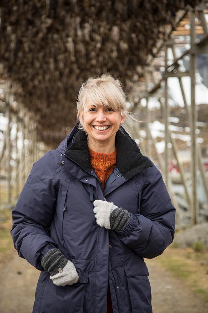 Ljusgårig Mat Tina ler strålande. Hon har en mörkblå jacka på sig och står under en ställning med torkad torsk i Lofoten Norge