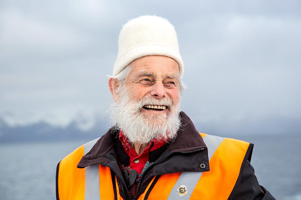 Leende gammal man med vit mössa och vitt skägg tittar snett till höger