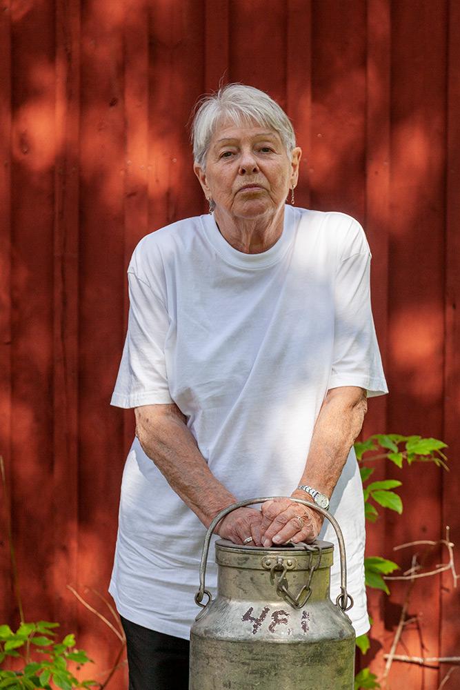 gammal kvinna i vit tröja står framför rödmålad tvävägg och håller händerna på en gammal mjölkkruka