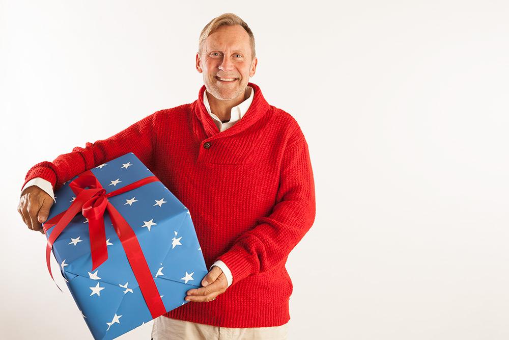 Glad ljushårig man med röd tröja håller ett stort blått paket med vita stjärnor på och ett rött band med stor rosett på under ena armen