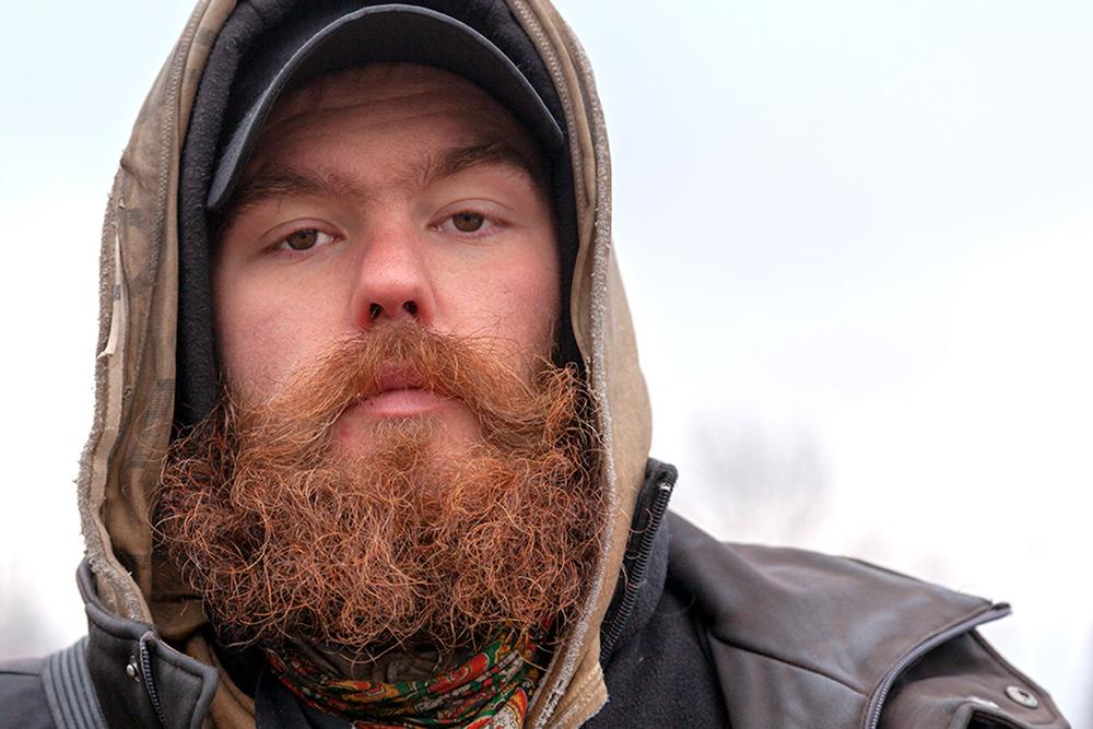 ansiktsbild av allvarlig man med keps och huva på huvudet. Han har rödbrun stor mustasch och yvigt krulligt skägg.