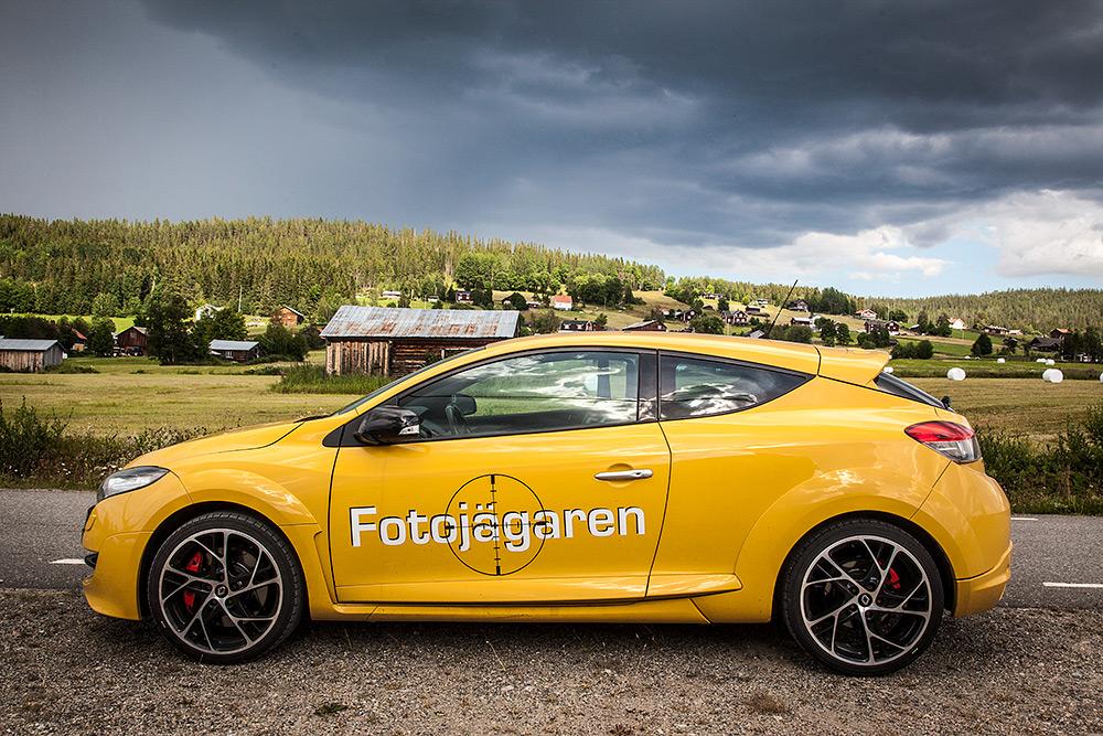 Gul sportbil på väggrenen framför jordbrukslandskap på landsbygden