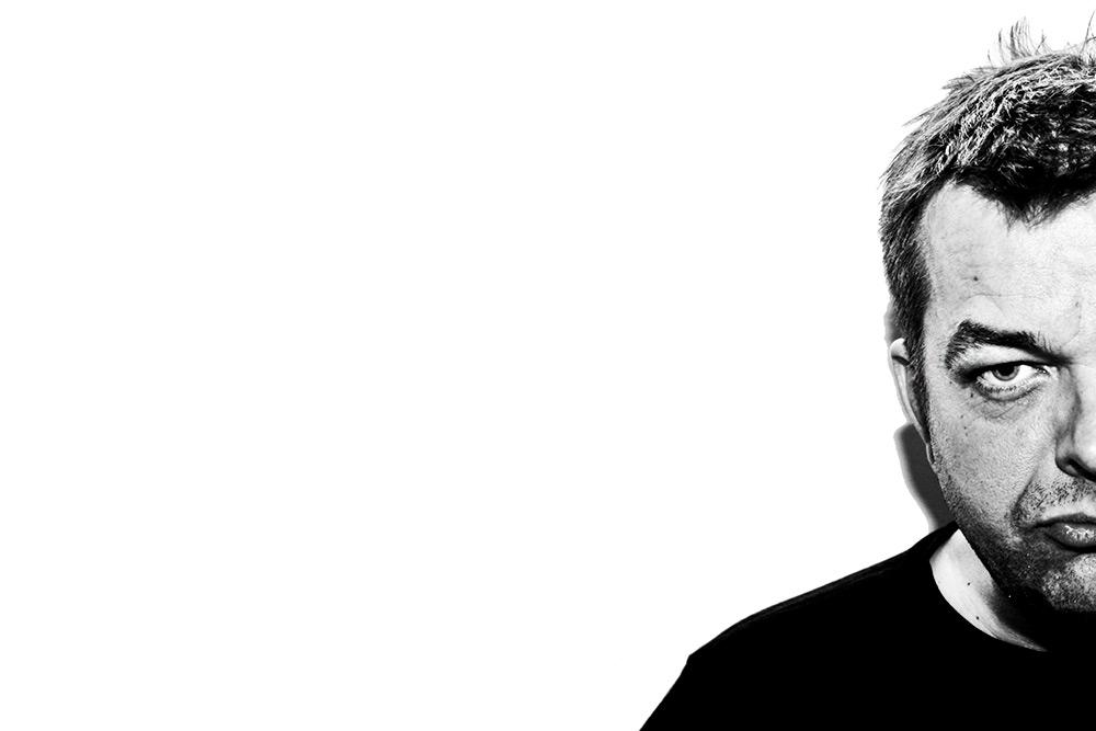svartvit bild på halvt ansikte på man med kort hår, intensiv blick, svart tröja