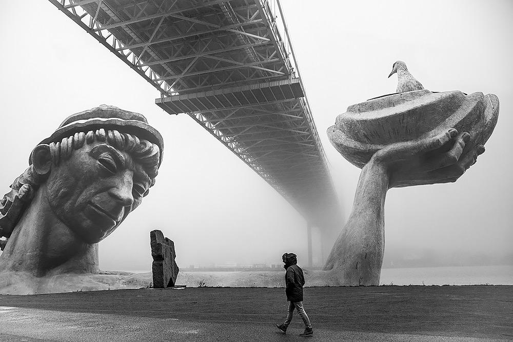 bildmontage statyn poseidon kommer upp ur vattnet under älvsborgsbon man ser huvudet och ena armen med ett kärl där en fågel sitter. Det är dimma och en man klädd i jacka med huvan uppdragen passerar under bron