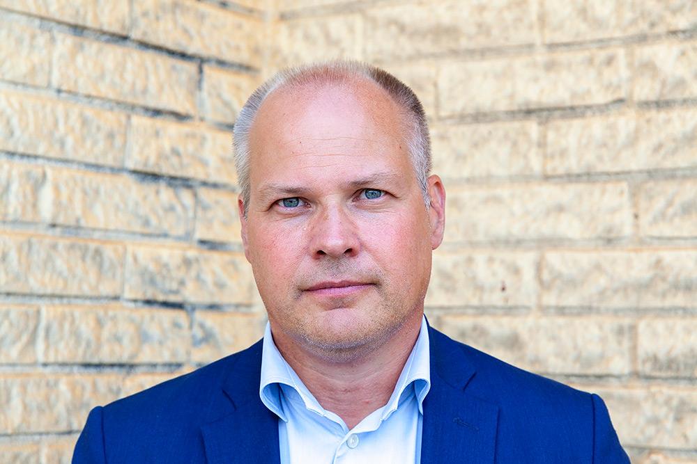 Framför en beige tegelvägg , Socialdemokraten Morgan Johansson, allvarlig, blåögd tunnhårig man med klarblå kavaj och vit skjorta.