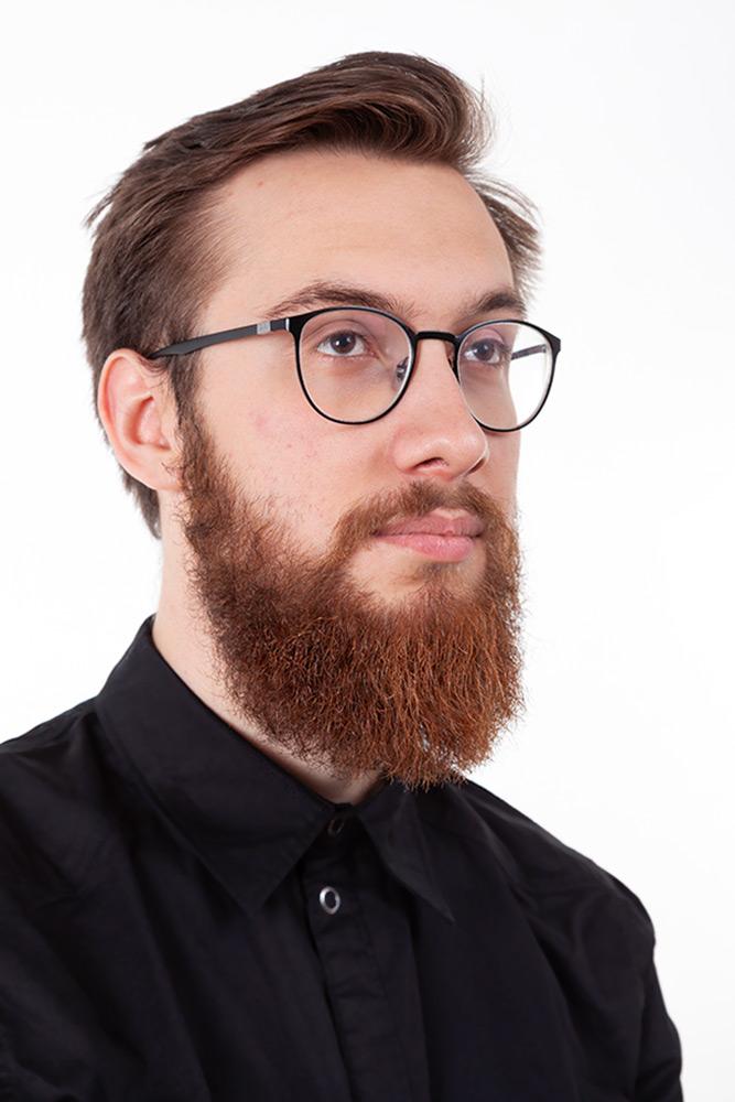 halvprofil bild av allvarlig ung man med kort brunt hår, svart skjorta och skägg