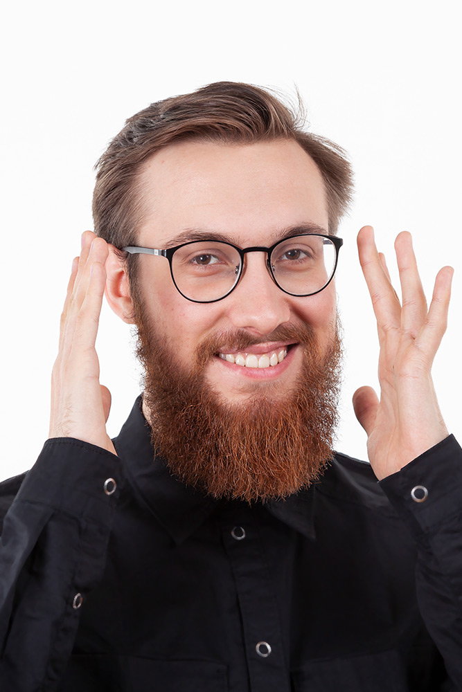 leende man med glasögon och kort brunt hår höjer händerna vid sitt ansikte