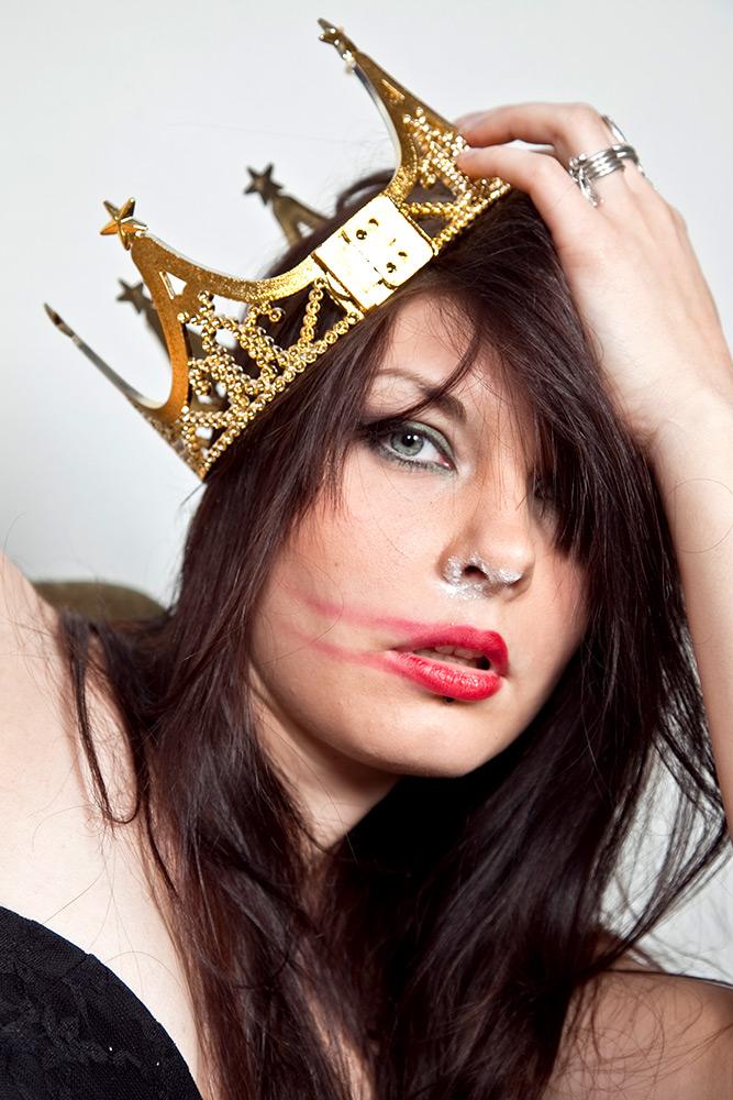 Partyprincessan. En kvinna med en krona som halkar på sned, hennes röda läppstift är utsmetat och näsan är full med vitt pulver