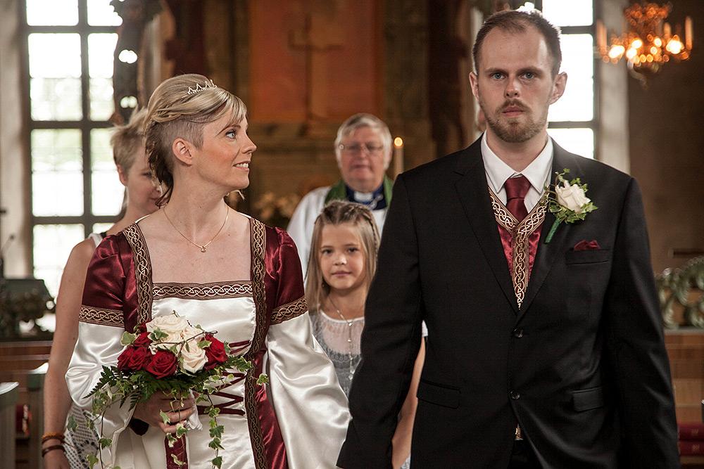 bröllopspar i kyrka. präst och brudnäbb skymtar bakom brud i profil med uppsatt hår och medeltidamönstrad klänning med bukett av röda och vita rosor. allvarlig brudgum med korthår och skägg, svart kavaj och vit ros