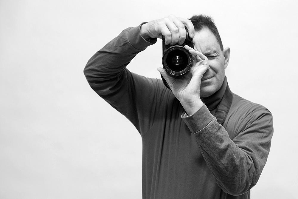 Svartvit halvkroppsbild av fotografernade man som håller kamera på högkant framför ansiktet, och vrider på fokusringen, blundar med ena ögat, ser fokuserad ut.