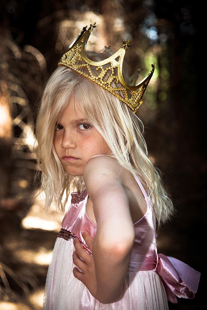 En ung flicka i rosa klänning står med armen i sidan, har en krona på huvudet. Hon har en allvarlig tuff uppsyn.