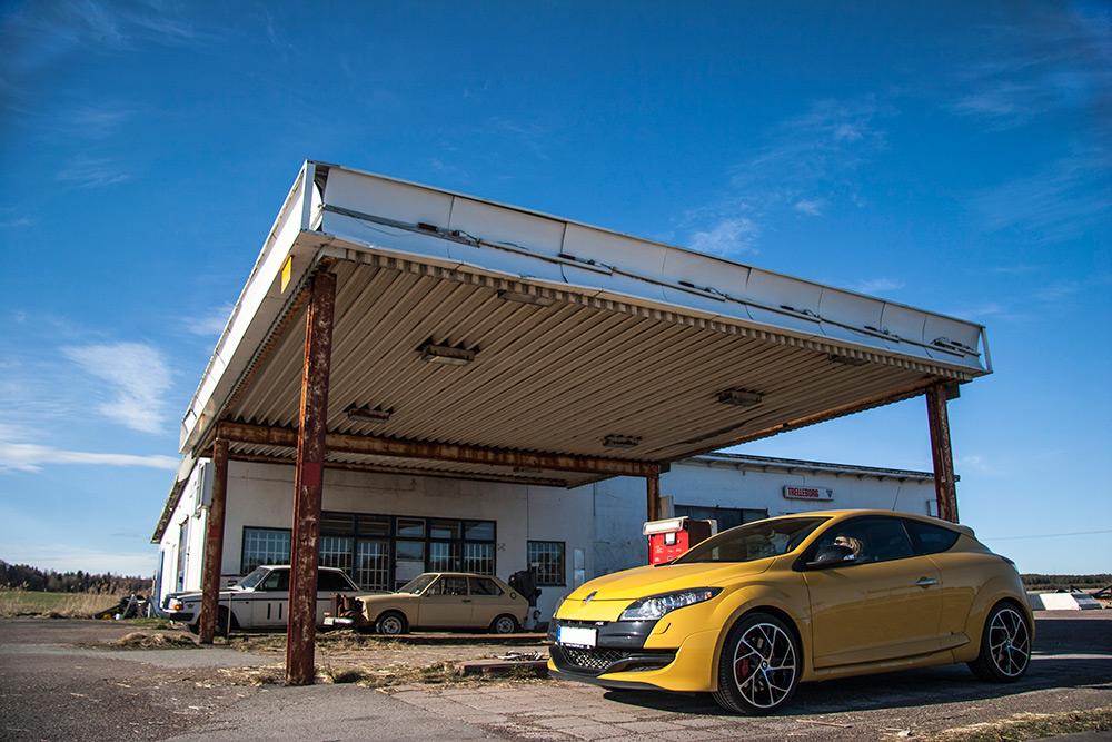 Blå himmel och en gul sportig Renault Megane RS står på en övergiven bensinmack som har igenbommade fönster.