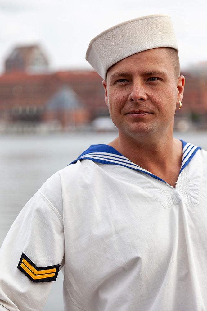 Halvkroppsbild på man med sjömansblus och sjömanshatt på snedden tittar åt vänster mot blurrig bakgrund