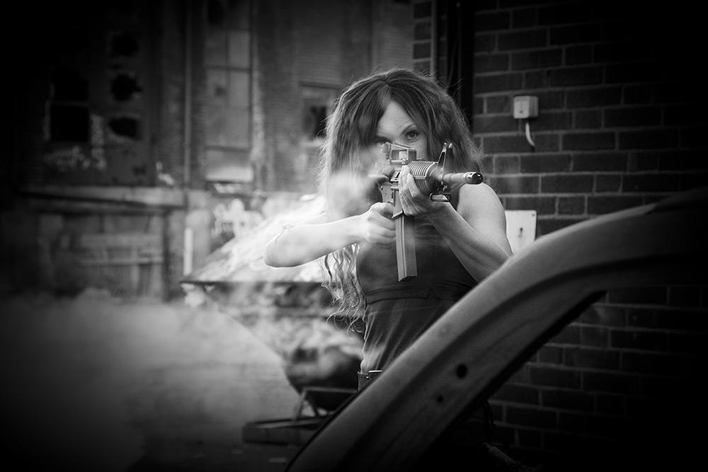 Svartvit bild. En kvinna siktar med ett maskingevär mot någonting. Det är rökigt och miljön är dystopisk.