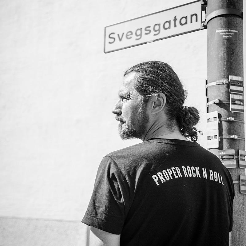 Man med knut i nacken och skägg, står och tittar till vänster, bär svart t-shirt där det står proper rock n roll på ryggen. Han står under gatuskylt där det står svegsgatan.