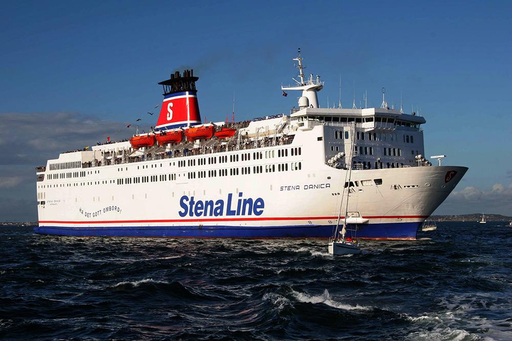 Blått hav med vita vågor och små segelbåtar. I mitten färjan Stena Danica mot blå himmel