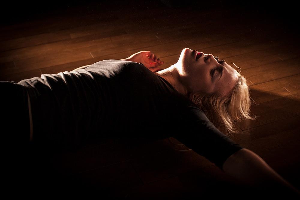 Teater. Motljus, kvinna ligger på trägolv och träffas av ljus så hennes form träder fram.