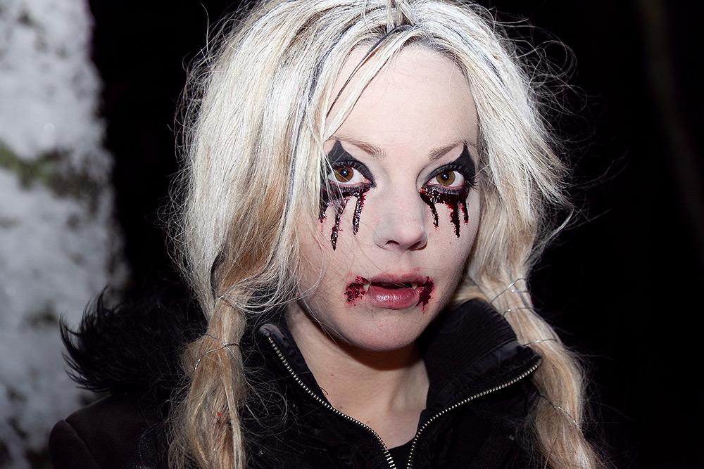 Flick-vampyr med ljus hår i flätor, svartsminkad runt ögonen, gråter blod och har sår i mungiporna.