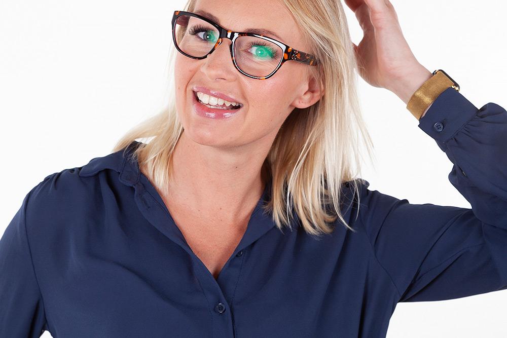 Halvkroppsbild på ljushårig leende kvinna i blå blus höjer handen och fixar med håret.