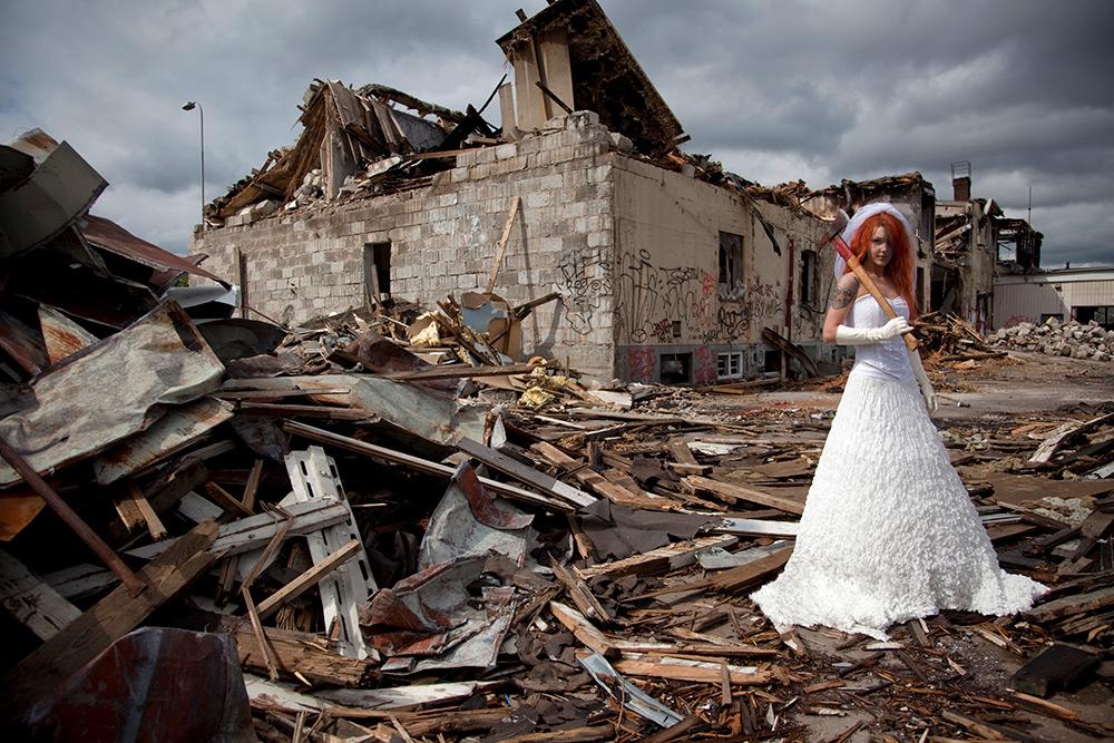 Brud med brandyxa över axeln, klädd i långa vita handskap och vit klänning utan ärmar, står på en rivningstomt med halvrivna hus och bråte