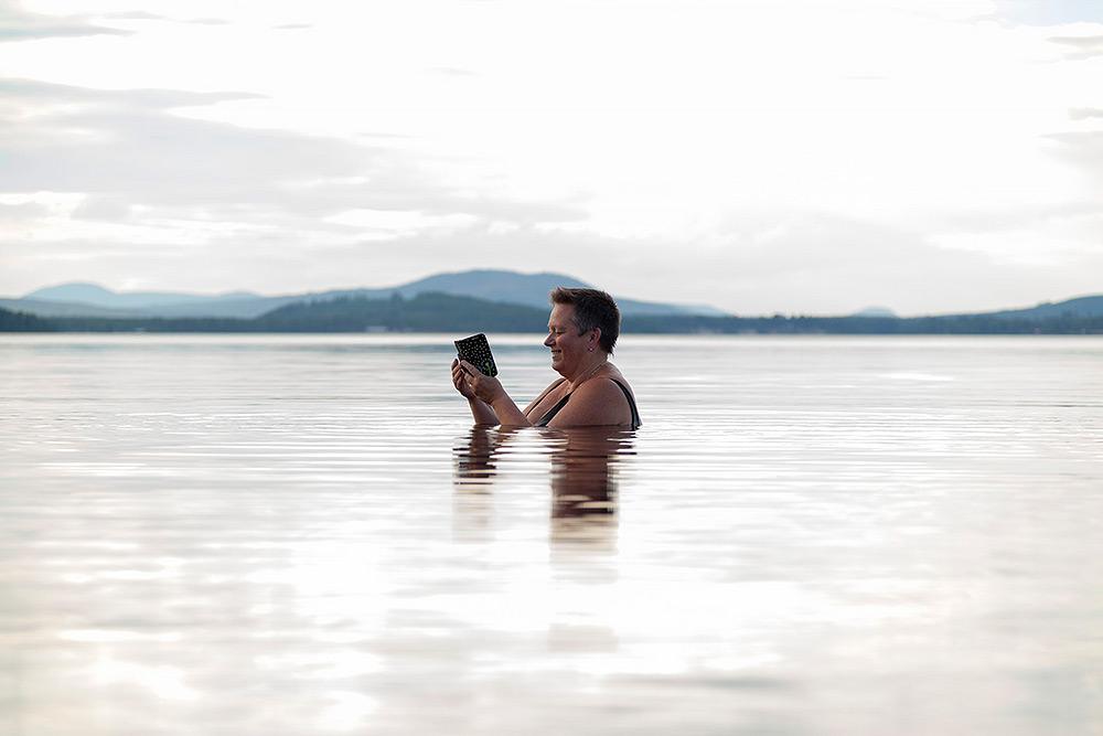blånande berg i bakgrunden. I den spegelblanka sjön står en medelålders kvinna med kort mörkt hår, med vatten upp till axelhöjd. Hon tittar leende in i sin mobiltelefon.