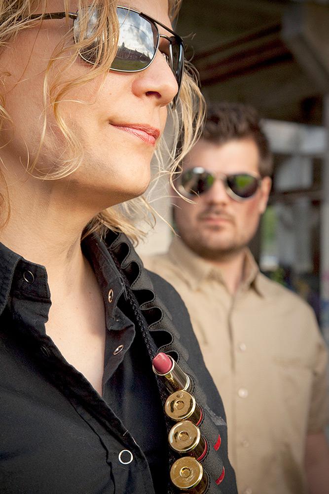 Närbild på kvinna med läppstift i sitt patronbälte. I bakgrunden syns en man med solglasögon