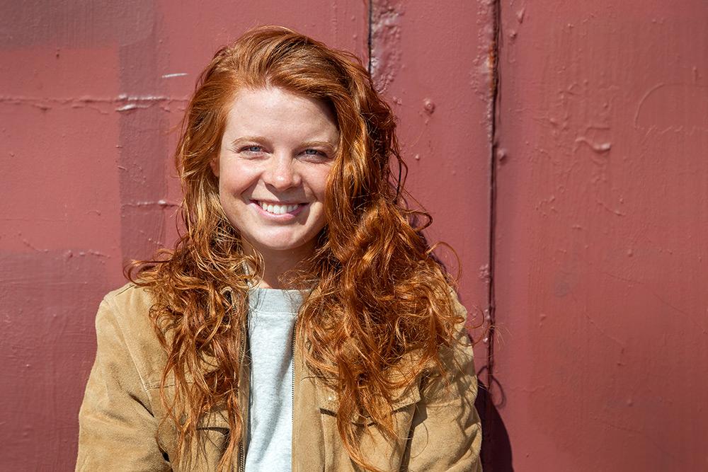 roströd bakgrund, halvkroppsbild på kvinna i beige mocca jacka. Hon har långt rött, burrigt, lockigt hår och ler så hennes vita tandrad blottas.
