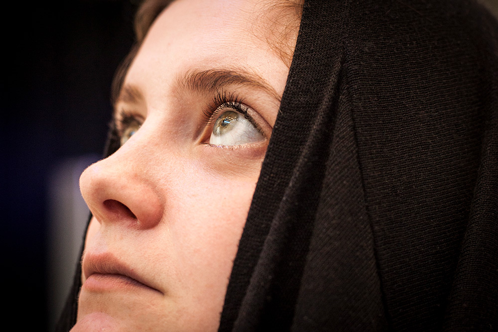 Del av ansikte på ung kvinna i profil som bär svart huva. Hon tittar uppåt.