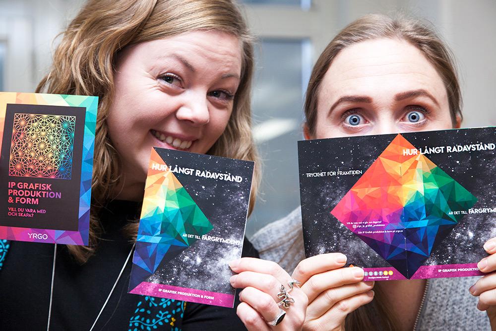 två kvinnor håller upp varsina broschyrer framför sina ansikten. Den ena ler och höjer ögonbrynen, den andra stirrar med stora ögon