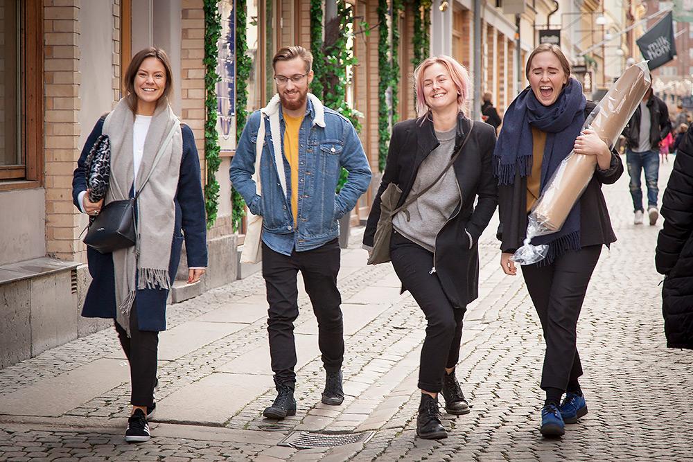 Tre glada unga kvinnor och en glad ung man går tillsammans på stans kullerstensgata