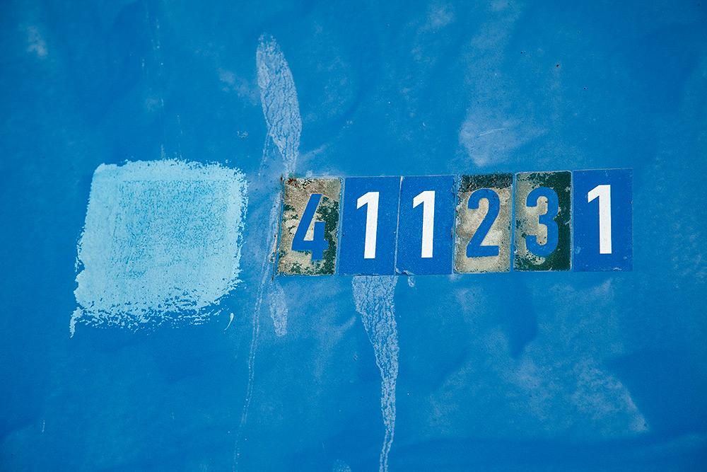 Detalj på container, olika nyanser av blått och siffrorna 411231 är ditklistrade på